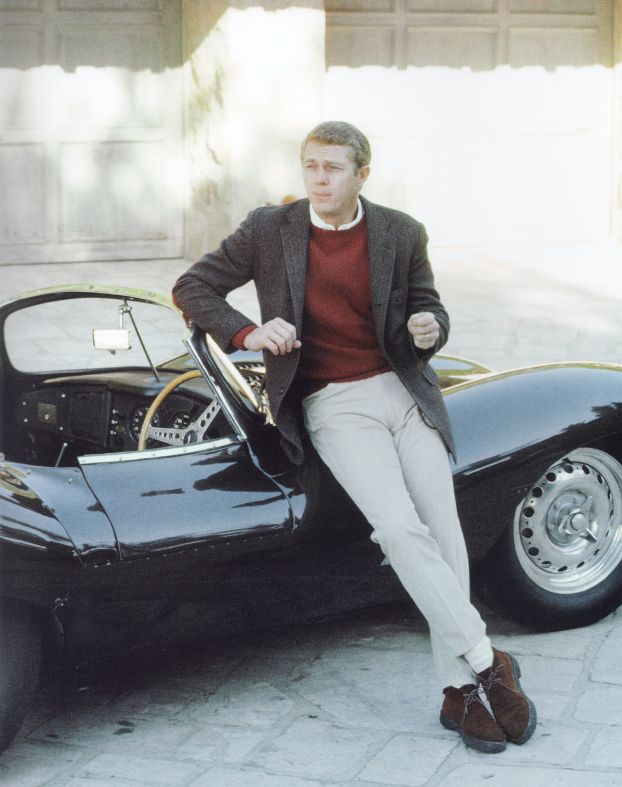 Steve McQueen wearing neutral chinos and blazer, resting against a vintage car