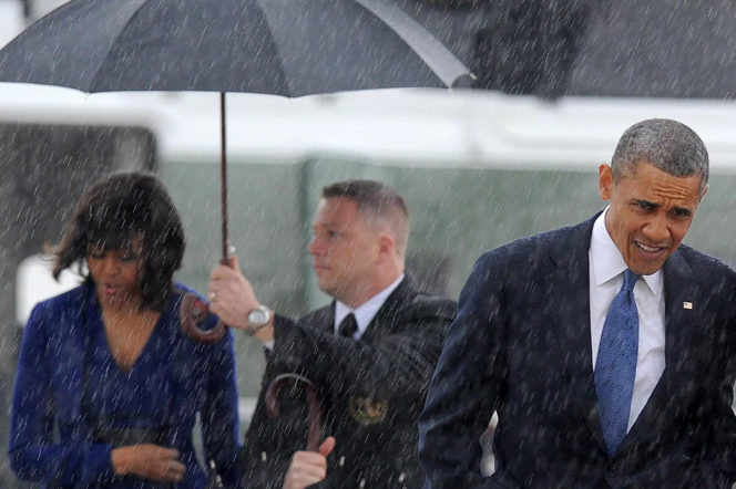 Barack Obama and Michelle Obama with an umbrella in the rain