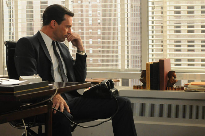 Don Draper with telephone thinking in office in Mad Men
