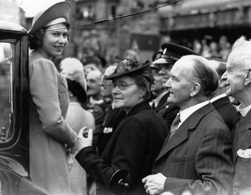 1945 - The Queen with members of the public in the East End of London. The date is 9th May 1945, the day after VE Day (Getty Images)