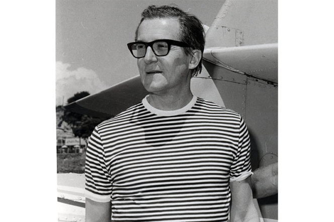 Photo of Hardy Amies in 1970 wearing striped t-shirt and spectacles