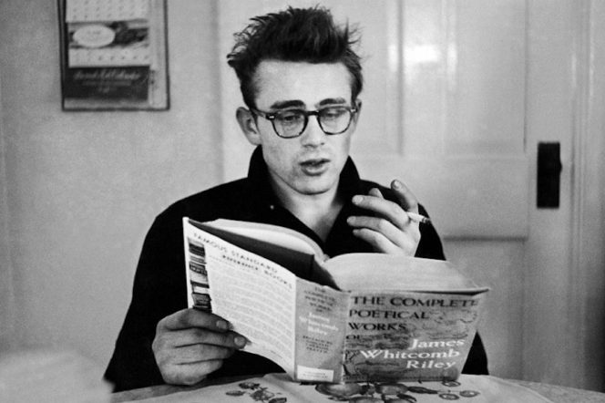 James Dean smoking and reading a book with glasses