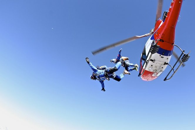 two sky divers jump out of a helicopter