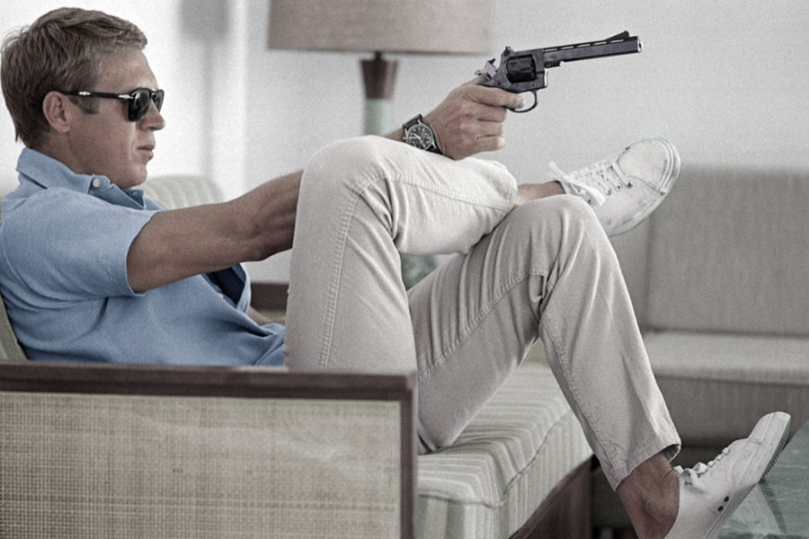 steve mcqueen wearing polo shirt and trainers pointing a gun