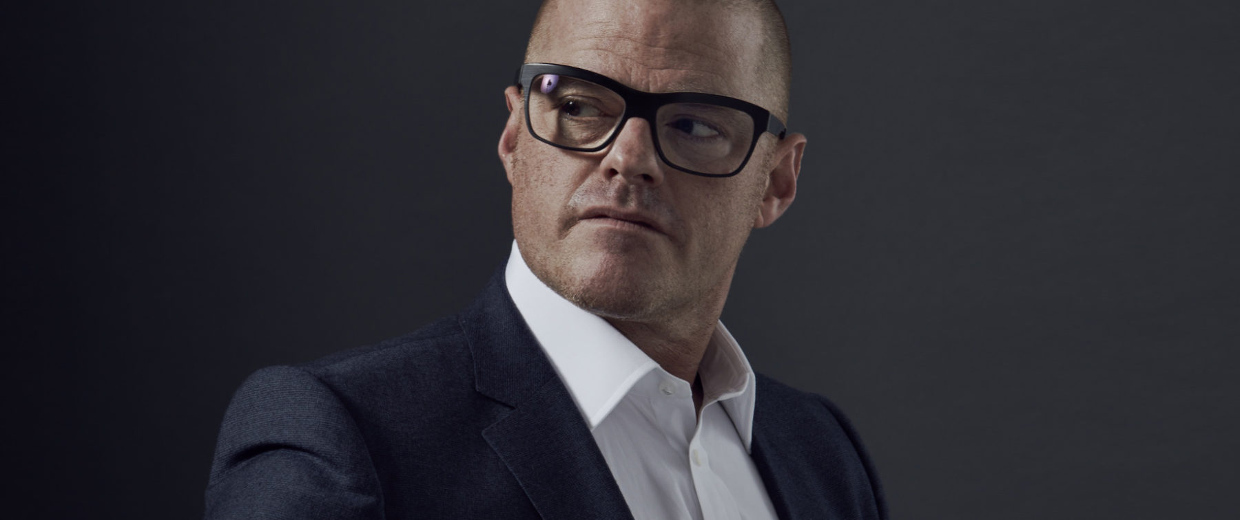 heston blumenthal wears glasses in a suit