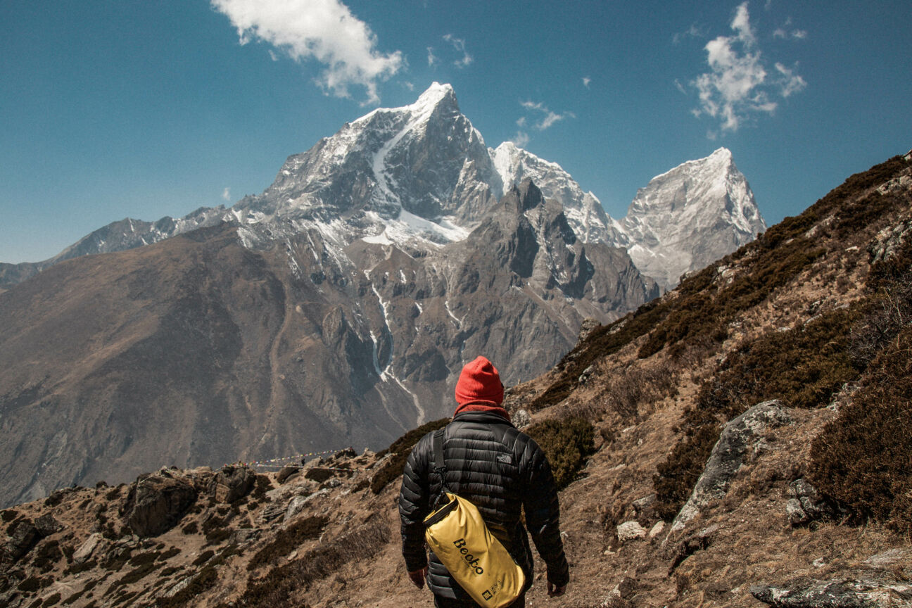 man stares out over mountain wearing hat