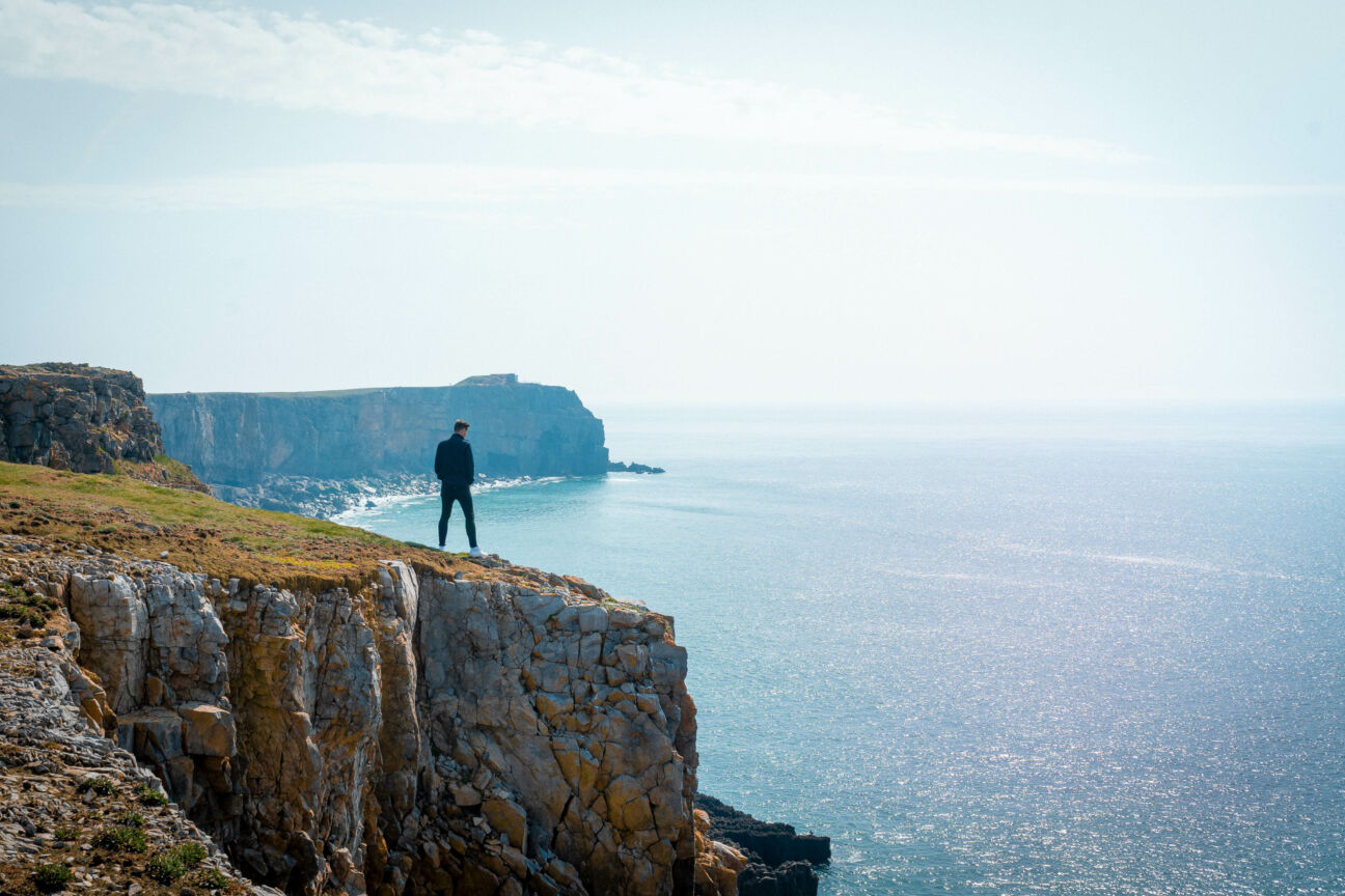 man looks over cliffs while coasteering