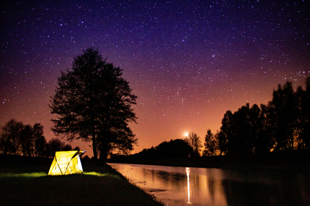 tent glows under stars and night sky while camping