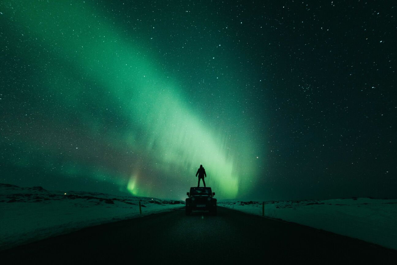man stands on top of jeep while northern lights and stars are in the night sky above