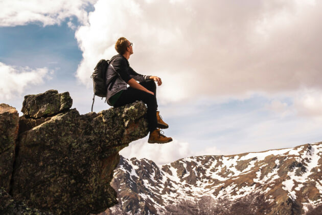 man sits on a crag on a mountain wearing boots and looking at the snow and sky
