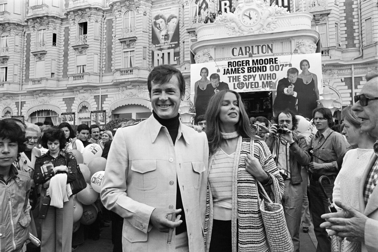 """British actor Roger Moore and US actress Barbara Bach pose outside the Carlton Hotel for the presentation of the film """"The spy who loved me"""" during the 30th Cannes Film Festival in Cannes, on May 20, 1977. (Photo by - / AFP) (Photo credit should read -/AFP via Getty Images)"""